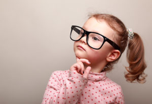 Cute kid girl in glasses thinking and looking serious